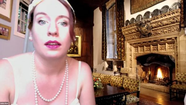 A suspect in a murder is virtually interogated by the guests. She is dressed in a '20s style with the backdrop of a nice 1600 mansion. The fireplace is roaring.